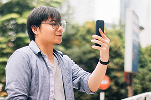 Young Asian man looking at cell phone.
