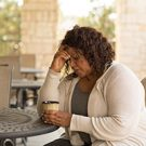 Female with a cup of coffee in deep thought.