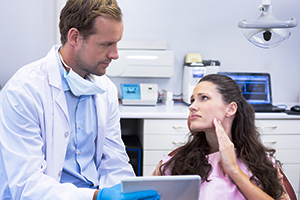 Dentist discussing findings over digital tablet with female patient
