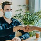 Colleagues in medical mask fist bump when meeting in office.