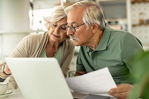 Senior couple analyzing their savings while going through home finances.