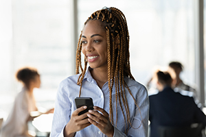 Smiling ethnic woman using cell phone while standing in office.