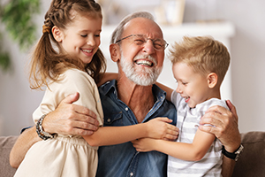 Grandfather laughing and hugging grandchildren on sofa