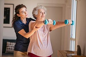 Senior woman using dumbbells with physical therapist's help.