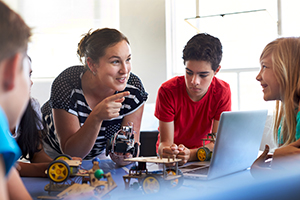 Teacher with student in after school program learning to program a robot vehicle.