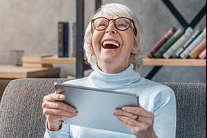 Happy senior woman looking and laughing at her digital tablet on sofa.